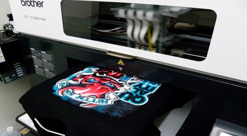 máquina de estamparia digital direta imprimindo em camiseta preta já costurada